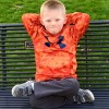 young boy on park bench with arms behind head