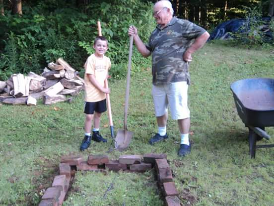 A young boy and his grandfather, they're both holding shovels.