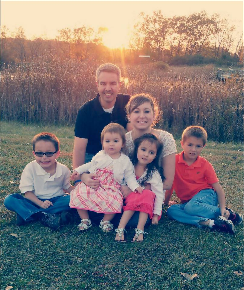 Family of six smiling at sunset.