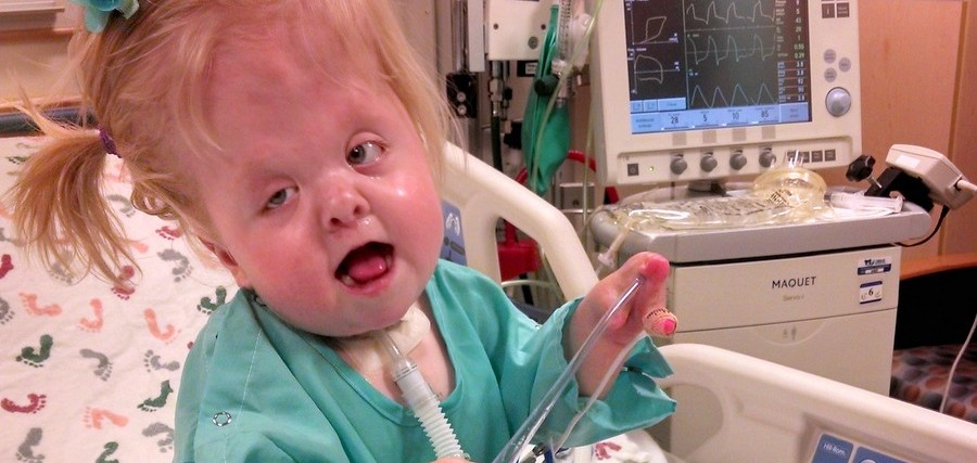 a young girl sitting on a bed in a hospital room