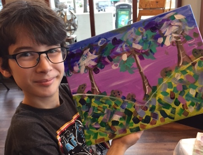 boy in glasses holding up colorful painting