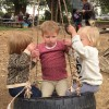 Three girls playing on a tire swing