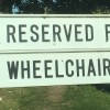 "A sign that says, :Reserved for wheelchair users,"" with the word fat graffited on it"