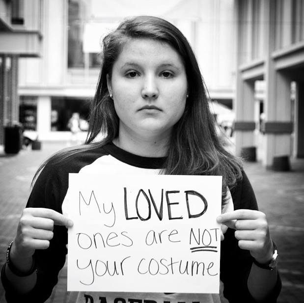 mental health advocate holds sign saying 'my loved ones are not your costume'