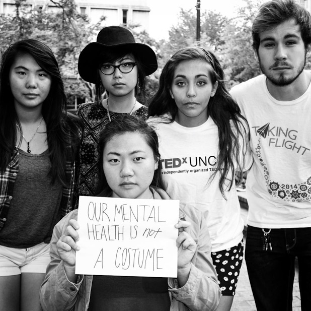 mental health advocates hold sign saying 'our mental health is NOT a costume'