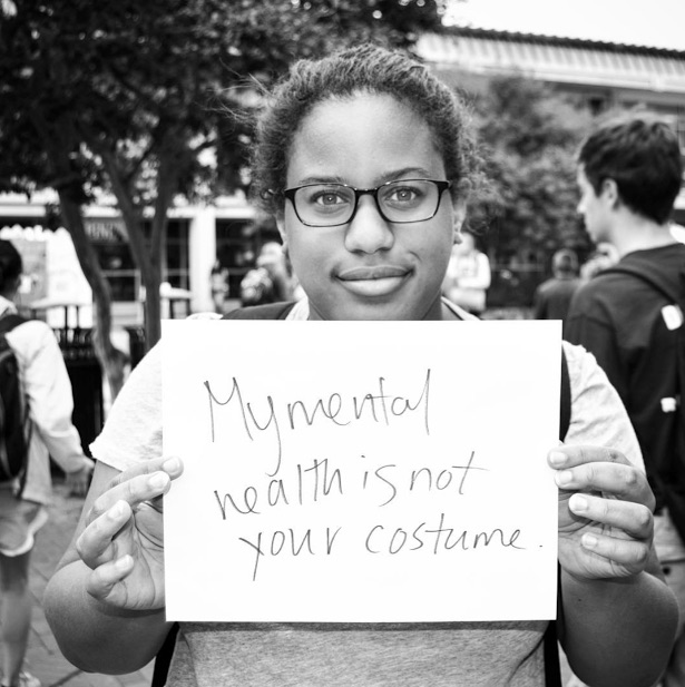 mental health advocate holds sign saying 'my mental health is not your costume'