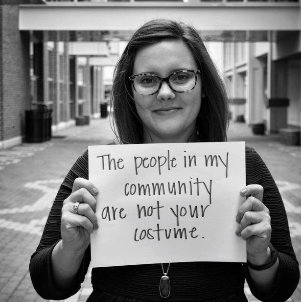 mental health advocate holds sign saying 'the people in my community are not your costume'