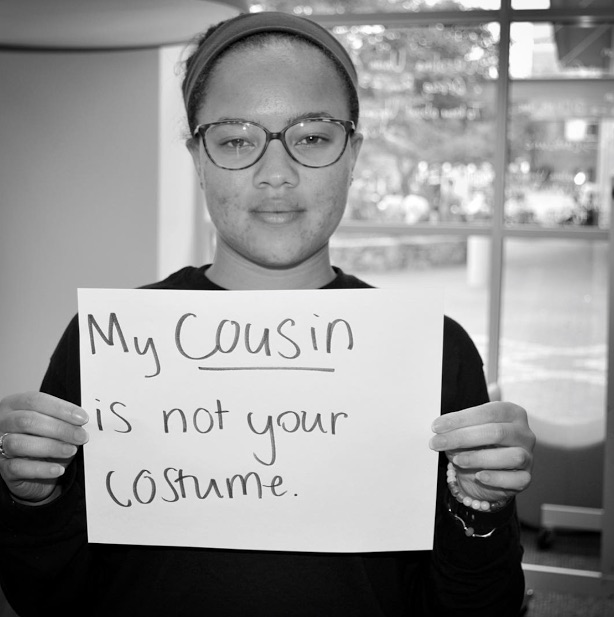mental health advocate holds sign saying 'my cousin is not your costume'