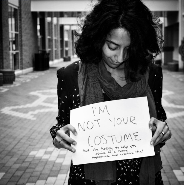 mental health advocate holds sign saying 'I'm not your costume, but I'm happy to help you think of a more appropriate and creative idea!'