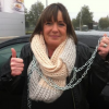 Woman gives a thumbs up as she is chained outside of a building