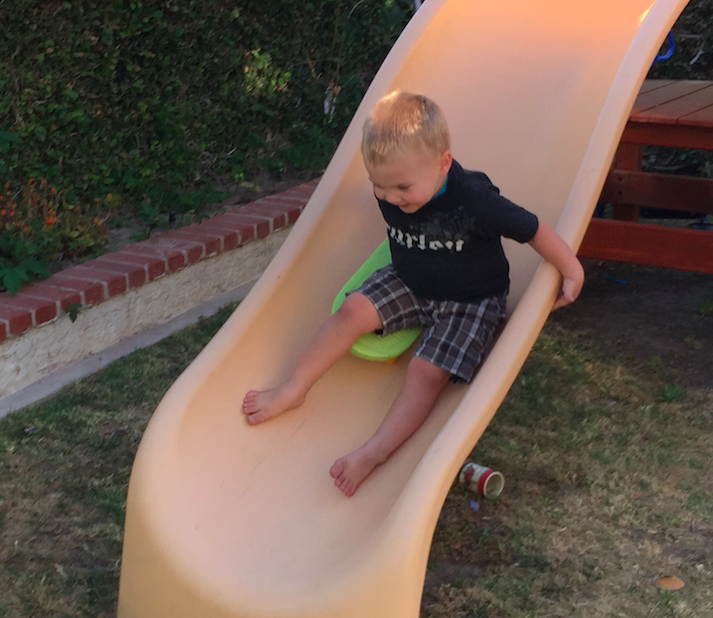Author's son sliding down slide