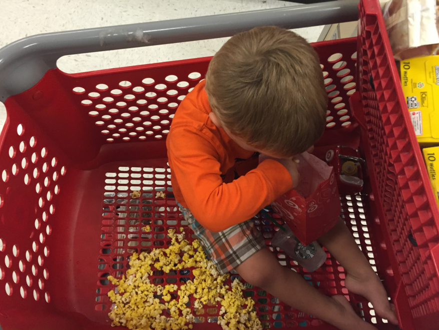author's son in target eating popcorn in the shopping cart