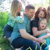 Gillian's family sitting on the grass in a park