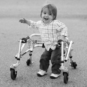 black and white photo of a toddler using a walker