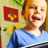 A smiling boy holding a book