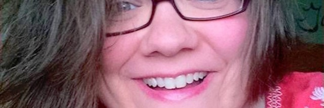 A woman with glasses smiling into camera