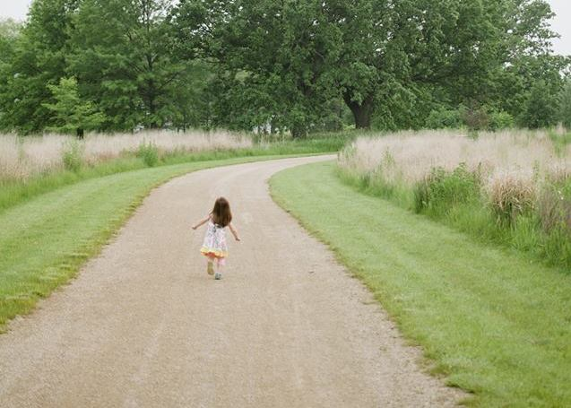 young girl walking down a path