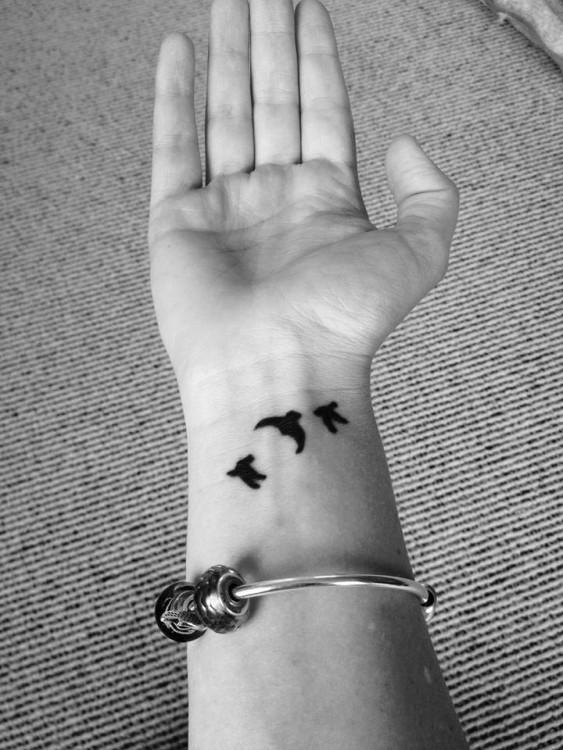 A tattoo of three birds on a wrist
