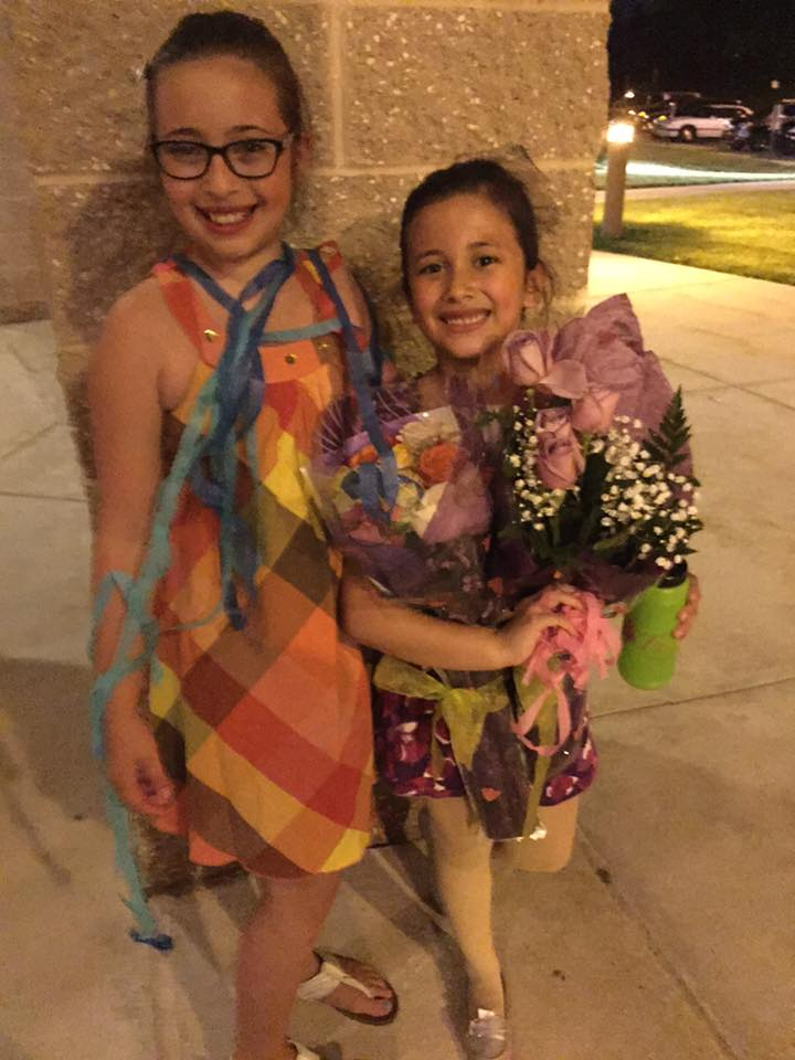 Two girls holding flowers.
