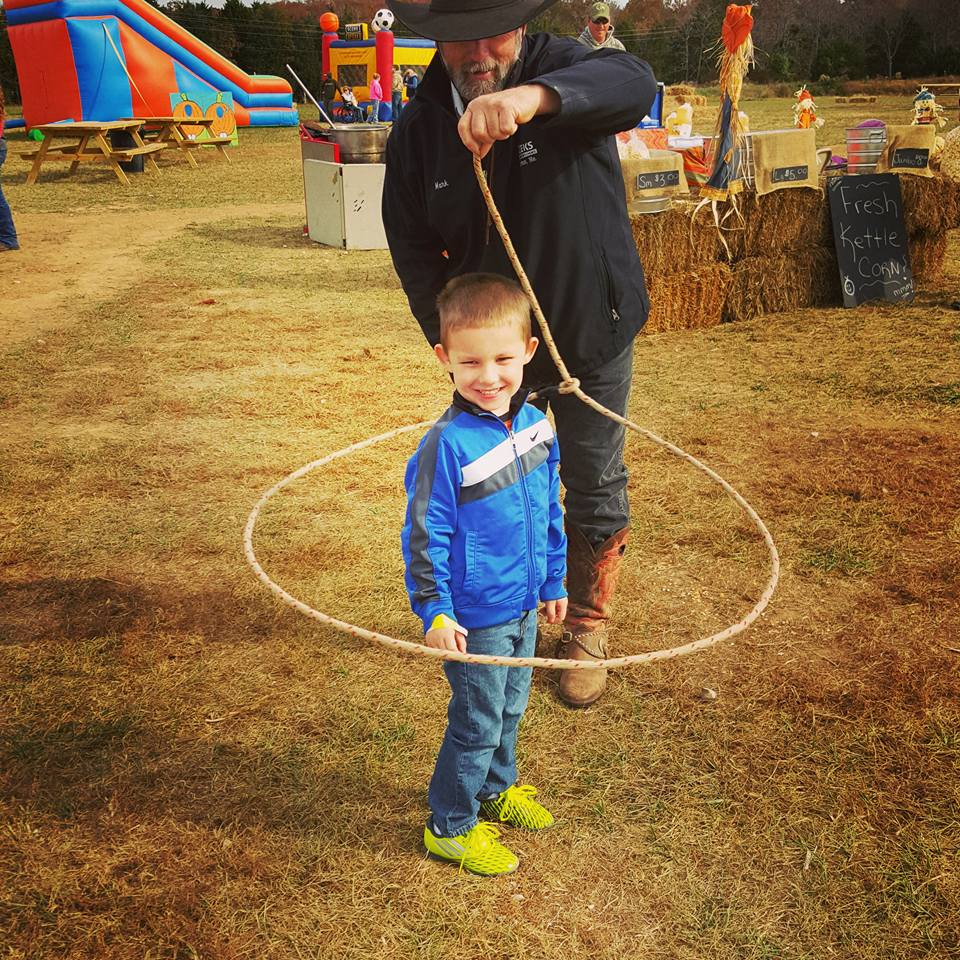 A cowboy swings a lasso around a little boy.