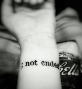 "Tattoo that says ""; not ended"" on wrist"