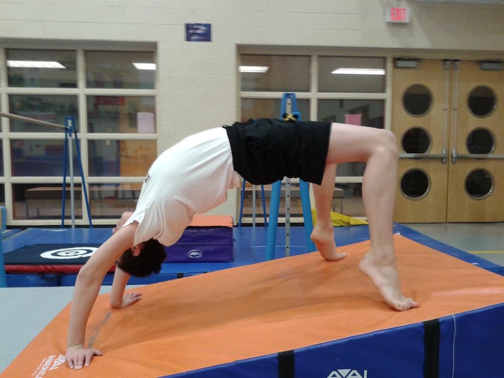 boy doing backbend in gymnasium