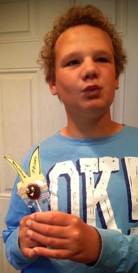 boy in blue shirt holding lollipop