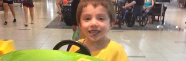 young boy smiling and playing on a ride at the mall