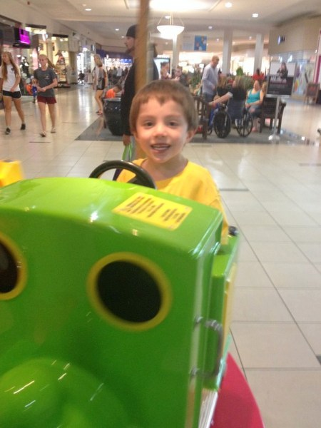 young boy with special needs smiling and playing on a ride at the mall