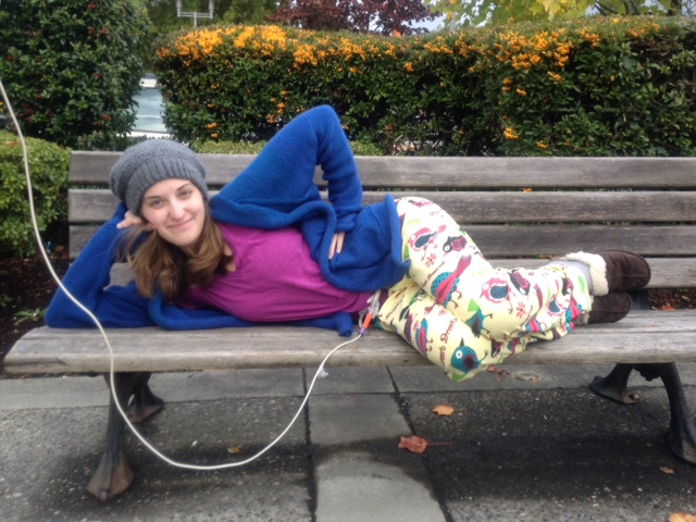 a woman hooked up to an IV lying on a park bench