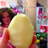 A closeup of a woman's hand holding a peeled potato with her daughter in the background