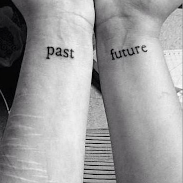 "The words ""past"" and ""future"" written on two wrists"