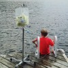 A boy with medical equipment nearby sits with feet hanging over a body of water at a pier