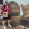 A woman stands in front of a mural painting of a male and female lion