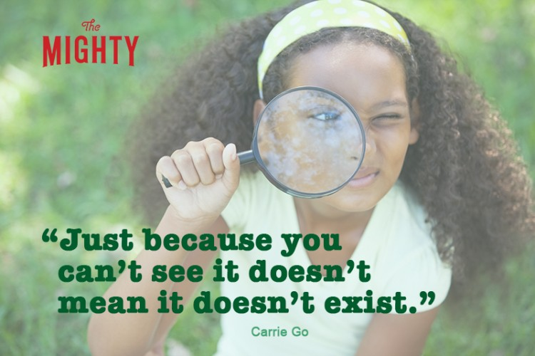 Young girl looking through magnifying glass in the park