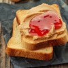 Peanut butter and strawberry jelly sandwich on wooden background