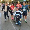 Runners push man in broken wheelchair to the end of the race