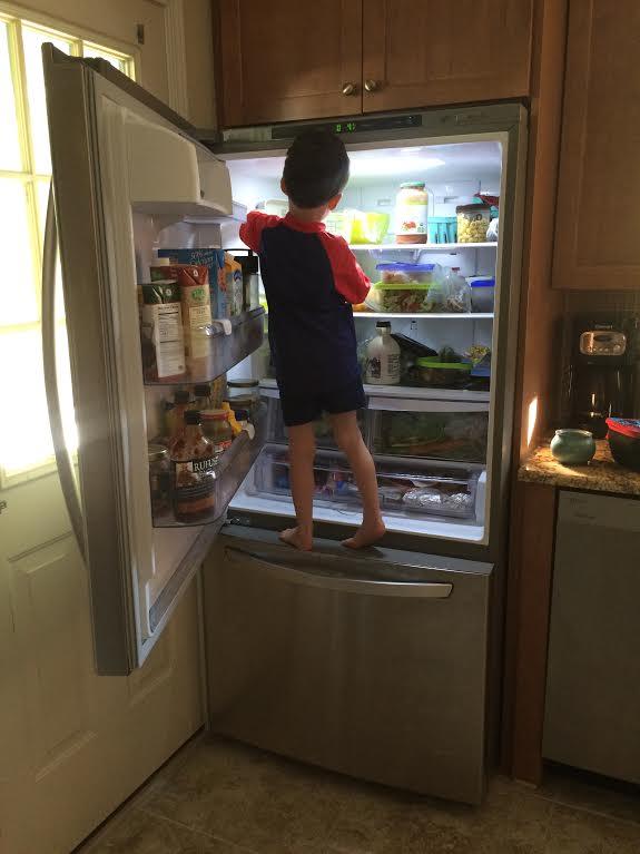 Boy standing in front of fridge with the door open