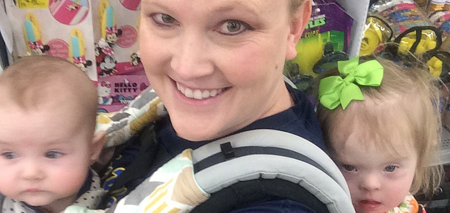 Mom smiles at camera with two babies strapped to her