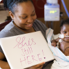 A mother next to her baby who's in a hospital bed. The mother holds up a sign that reads: she's still here.