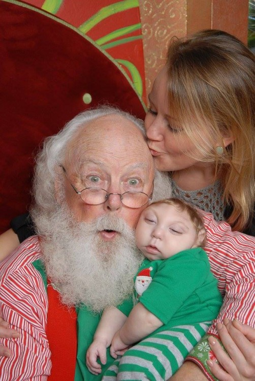 mother kissing santa's forehead while he holds her son