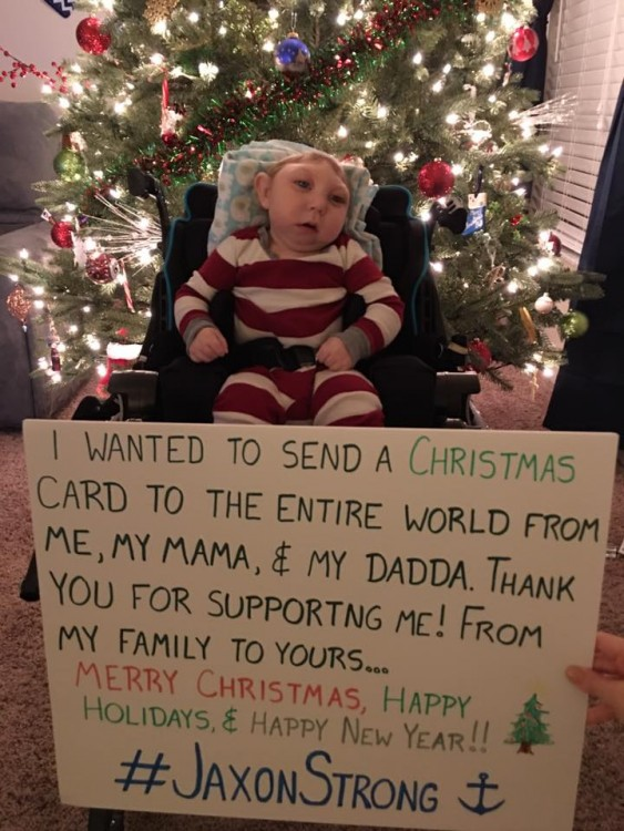"author's son in front of christmas tree with sign that says ""I wanted to send a christmas card to the entire world from me, my mama, and dadda. Thank you for supporting me. Happy Holidays and Happy New Year. #JaxonStrong."""