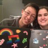 A young man with glasses and a young woman with dark, short hair hold up their artwork as they smile for camera