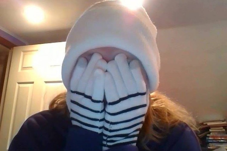 The author is wearing a white winter hat and stripped white and black gloves. She covers her face with her gloved hands.
