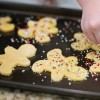 An upclose photo of a hand adding sprinkless to a baking sheet of cookies