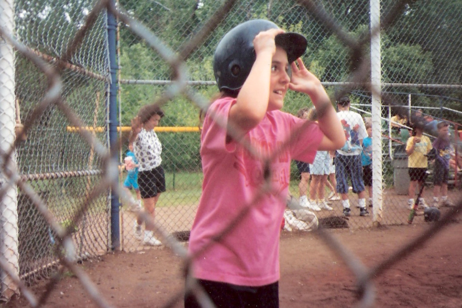 A close up of a girl playing softball through the holes of a gate