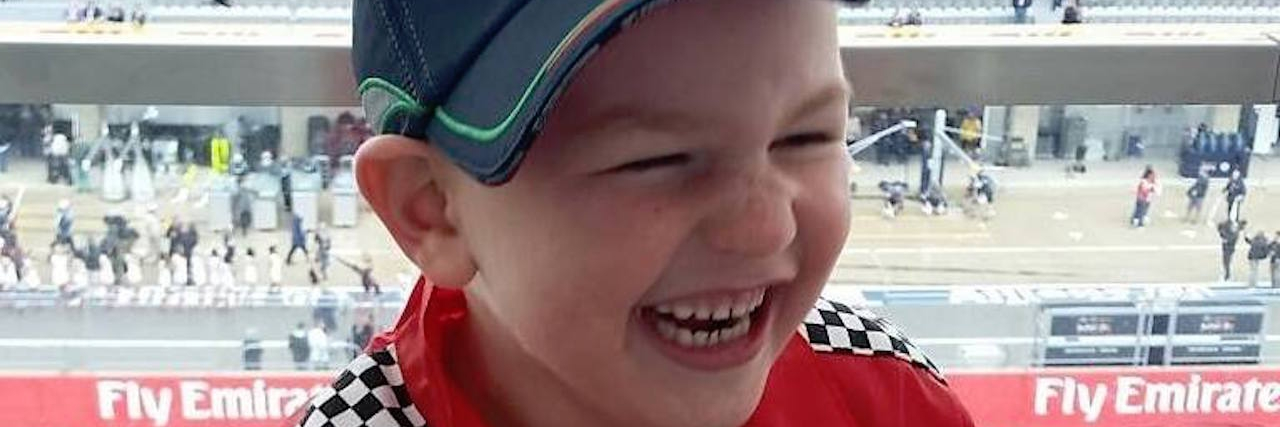 young boy laughing and wearing racing gear