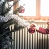 child hanging ornament on Christmas tree