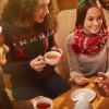 Happy young friends having tea and talking on Christmas evening