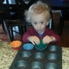 Small boy at counter in kitchen making cupcakes